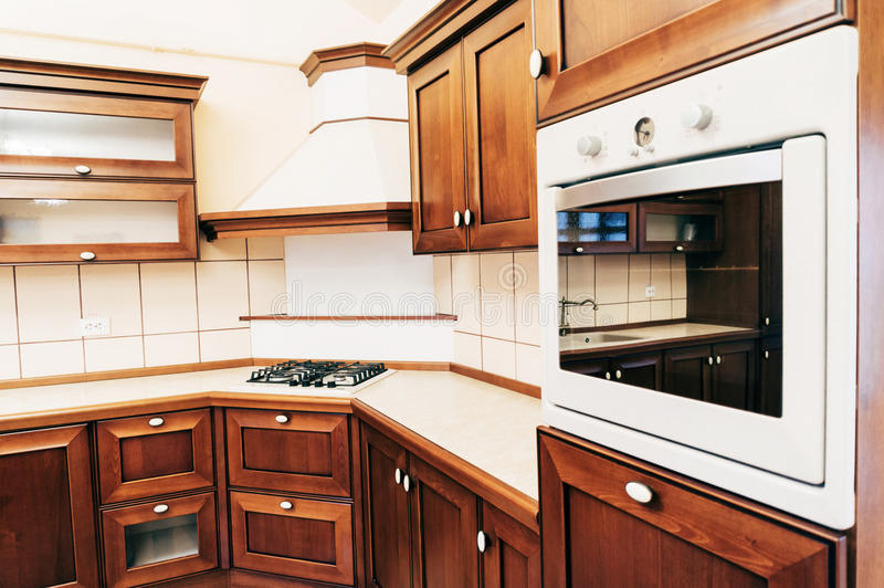 Kitchen interior. Interior of empty kitchen with oven, range and wood cabinets royalty free stock photography