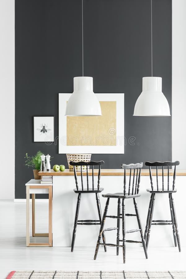 Kitchen with western bar stools. Modern kitchen with bar stools in western style at kitchen island against black wall with gold painting stock photos