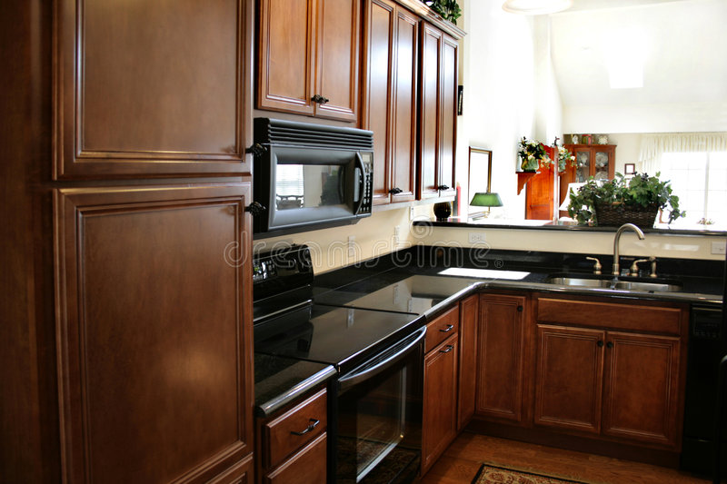 Kitchen wood cabinets black and stainless stove royalty free stock images