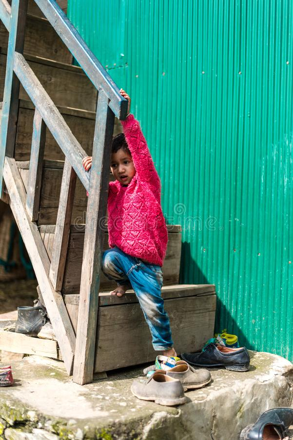 Kullu, Himachal Pradesh, India - September 01, 2018 : Himalayan kid at Stairs of traditional wooden house in mountain stock photos