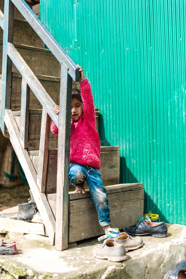 Kullu, Himachal Pradesh, India - September 01, 2018 : Himalayan kid at Stairs of traditional wooden house in mountain stock images