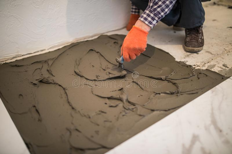 Laying Ceramic Tiles. Master make concrete floor in preparation for laying floor tile. Laying Ceramic Tiles. Troweling mortar onto a concrete floor in stock photography