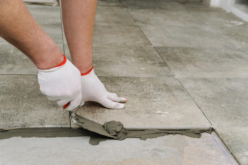 Laying Ceramic Tiles. Troweling mortar onto a concrete floor in preparation for laying floor tile stock photography