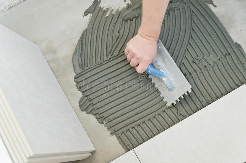 Laying Ceramic Tiles. Troweling mortar onto a concrete floor in preparation for laying white floor tile royalty free stock images