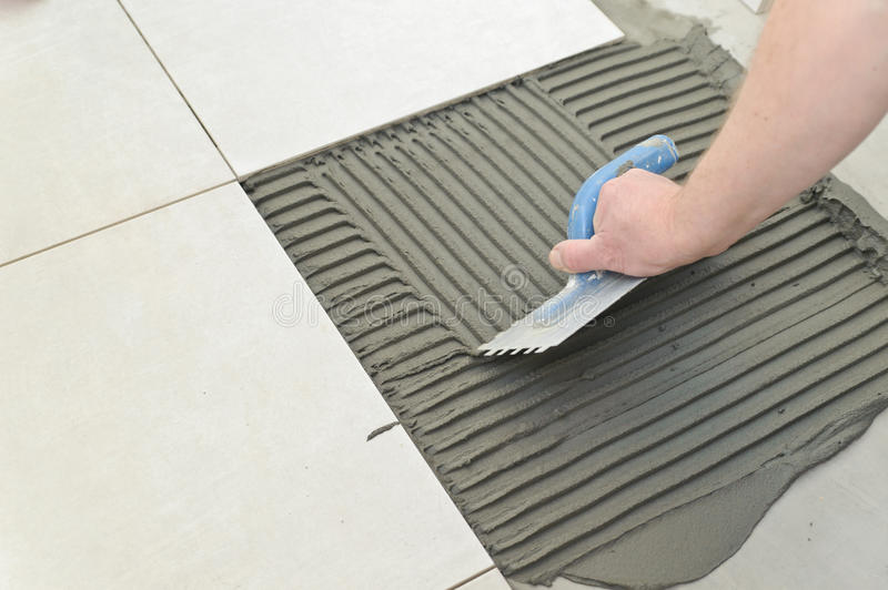 Laying Ceramic Tiles. Troweling mortar onto a concrete floor in preparation for laying white floor tile royalty free stock photos