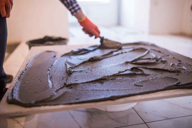 Laying Ceramic Tiles. Worker make preparation for laying floor tile. Laying Ceramic Tiles. Troweling mortar onto a concrete floor in preparation for laying royalty free stock images