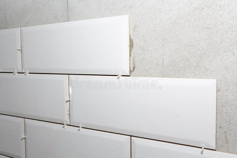 Laying tiles on the wall with gaskets, repair work royalty free stock photo