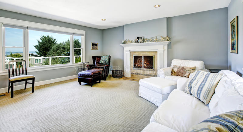 Light blue living room with white sofa and fireplace. Light blue living room with white sofa, armchair and leather chair and cozy fireplace royalty free stock photos