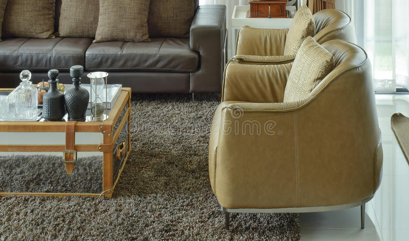 Light brown leather armchairs and dark brown leather sofa in the living room royalty free stock images