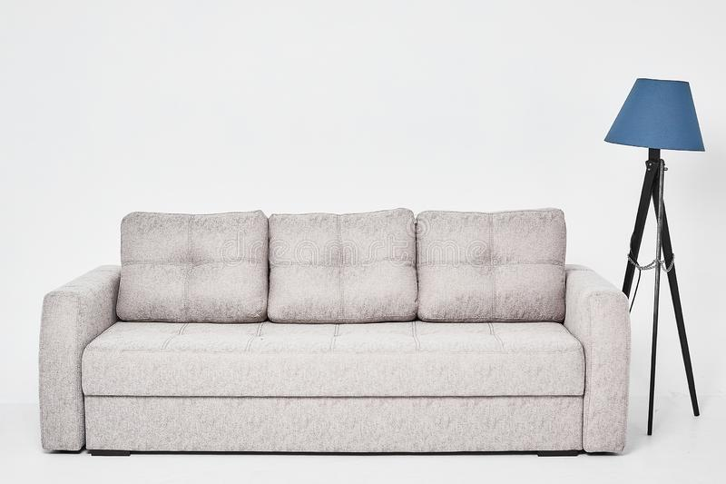Light grey classic sofa with three pillows and blue floor lamp, isolated at white background.  royalty free stock photos