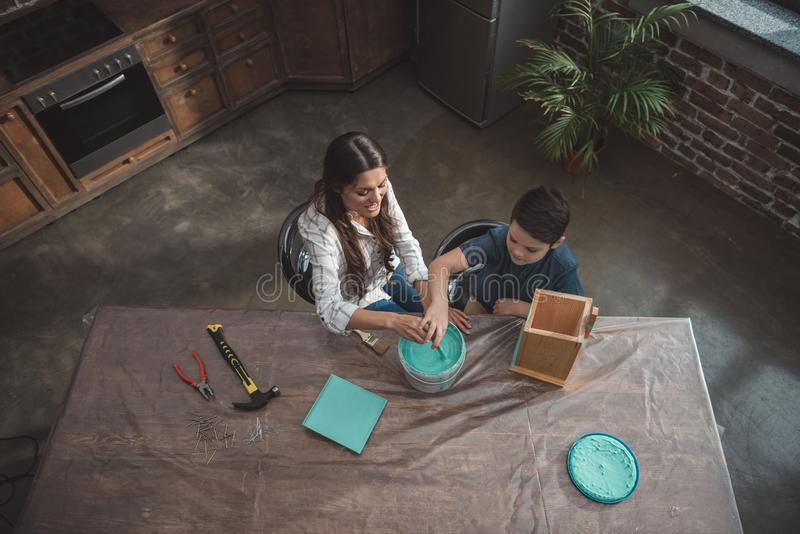 Little son and his beautiful mother sitting at kitchen table and painting a. Wooden birdhouse royalty free stock image
