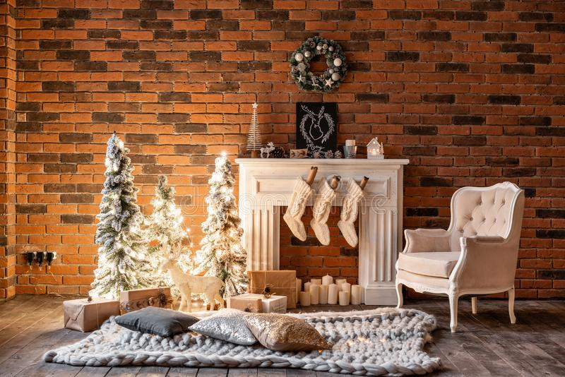 Loft apartments, brick wall with candles and Christmas tree wreath. White wool socks for Santa on the fireplace. Knitted. White wool socks for Santa on the stock image