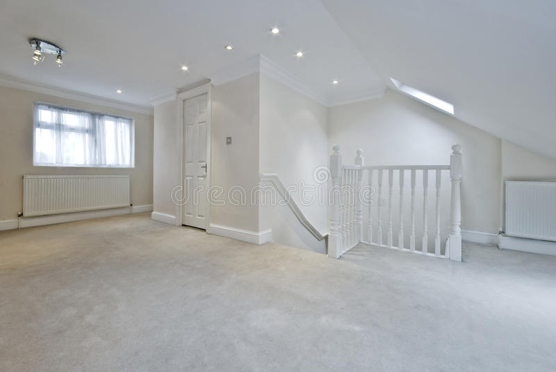 Loft room. With suite bath room and stairs with white wooden rails stock photography
