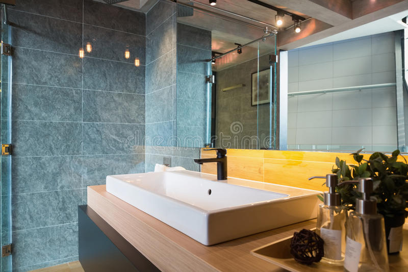 Loft style bathroom. Glass Shower box and white ceramic sink in a loft style bathroom royalty free stock photography