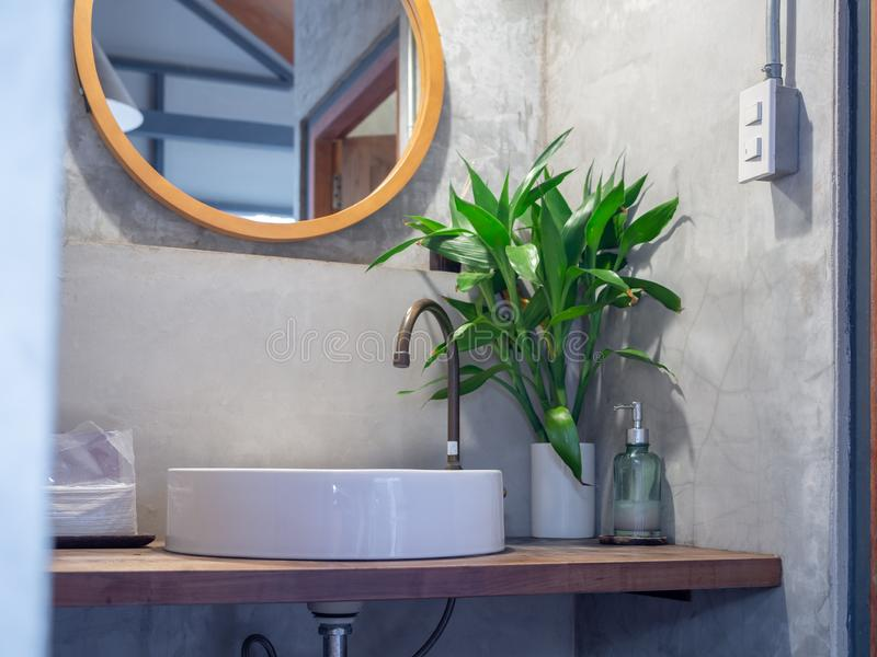 Loft style bathroom interior. Brass faucet with white sink basin, green leaves in ceramic vase and liquid hand wash soap bottle on. Bangkok, Thailand - December stock photography