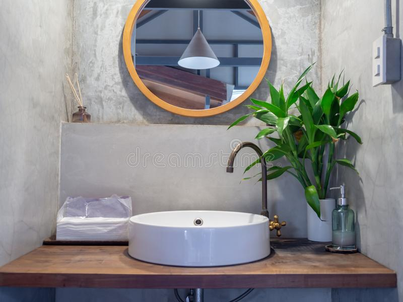 Loft style bathroom interior. Round mirror on concrete wall with brass faucet, white sink basin, green leaves in ceramic vase and. Bangkok, Thailand - December 1 royalty free stock photography