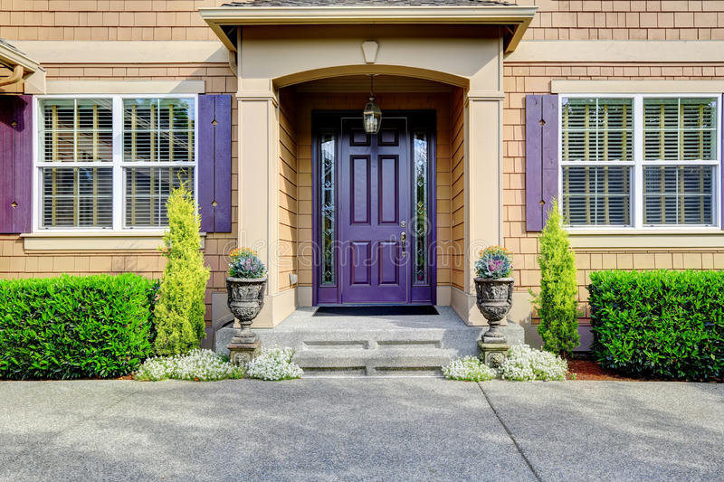Luxury house exterior. Entrance porch with purple door. Luxury house. Clapboard siding exterior with purple elements. Entrance porch with trimmed hedgeds along royalty free stock image