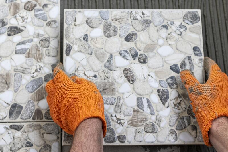 Male hands with tile and glue on wall. Work of laying tiles. stock images