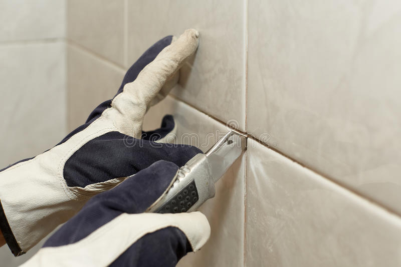 Male worker tiling a wall. stock images