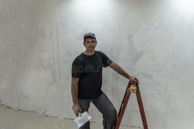 Man doing repairs, finishing room, plasterers, puttied and painted walls royalty free stock photos