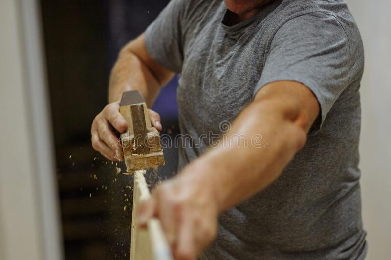 Man hands grinding the clapboard. Man working with wood. Home repair. Texture. Man hands grinding the clapboard. Man working with wood. Home repair. High quality royalty free stock photos