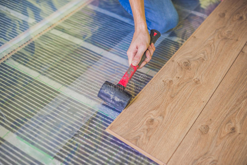 Man installing new wooden laminate flooring. infrared floor heating system under laminate floor royalty free stock images