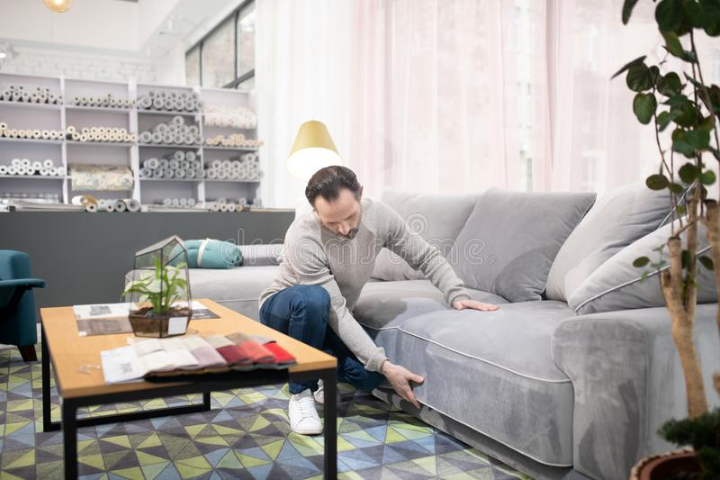 Man in light sweater and jeans examining the sofa. Before buying. Man in light sweater and jeans examining the sofa royalty free stock images