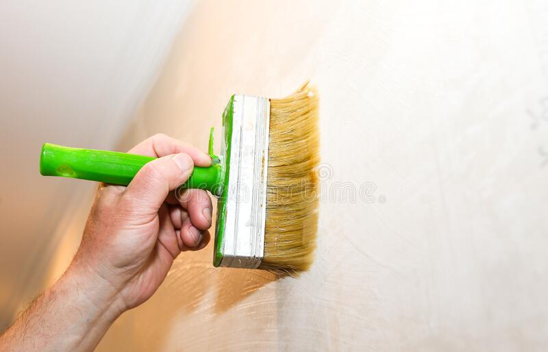 Man is putting glue on the wall with brush. Wallpaper hanging. Maintenance repair works renovation in the flat. Restoration royalty free stock photo
