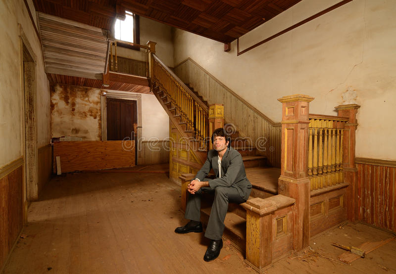 Man Sitting on Stairs in an Old House. Msn in suit sitting on the stairs of an old abandoned house royalty free stock images