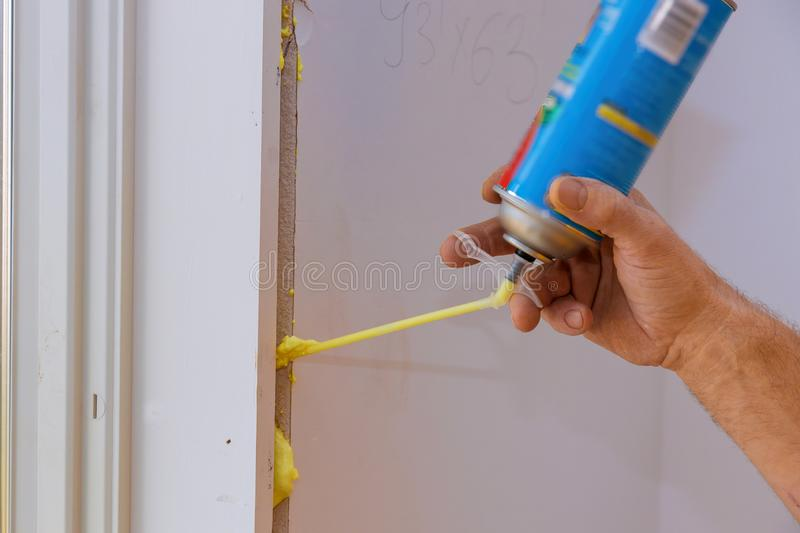 Man using polyurethane foam for installing a window on a handsome worker in action royalty free stock image