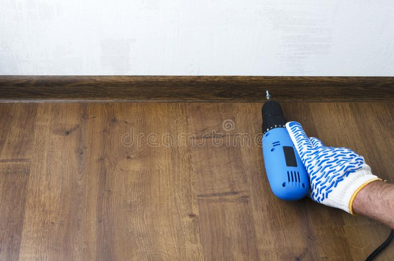 Man using a screwdriver for floor skirting board,plinth.Concept of repair.Empty space for text royalty free stock photography