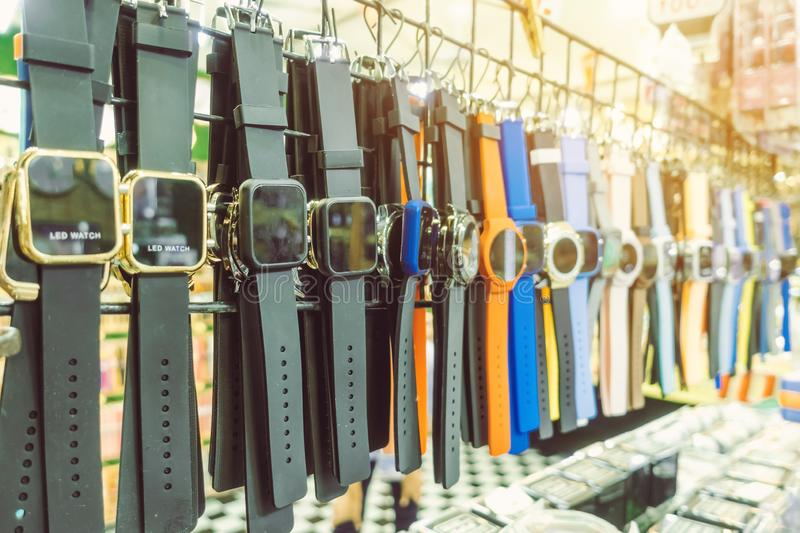 Many modern wrist watchs hang on to show and inexpensive for sale in local market. Selective focus stock image