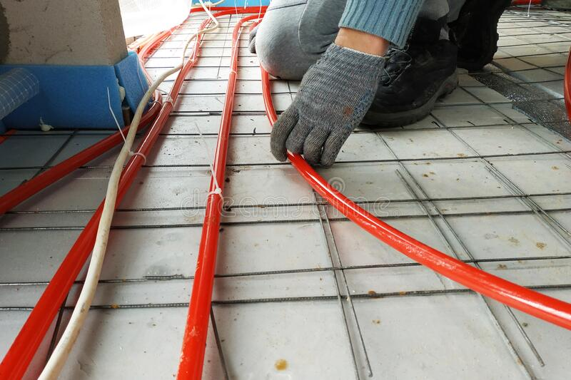The master laid pipes on the floor for heating and floor heating stock image