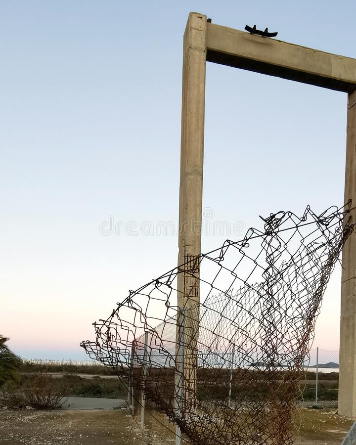 Mesh netting and concrete frame on sunset background. Concept freedom stock image