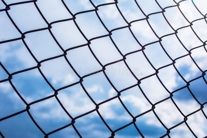 Metal black fence-mesh netting. Blue and white clouds on blue sky. The background image of the fence. Selective focus stock photo
