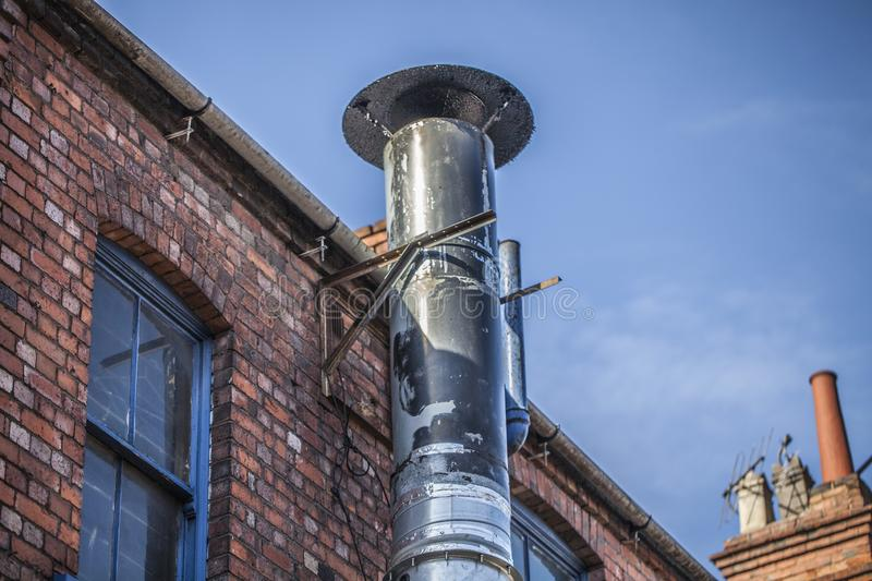 Metal chimney on the old brick house. Ventilation tube chimney on the red brick house. Blue sky in the background. royalty free stock photo