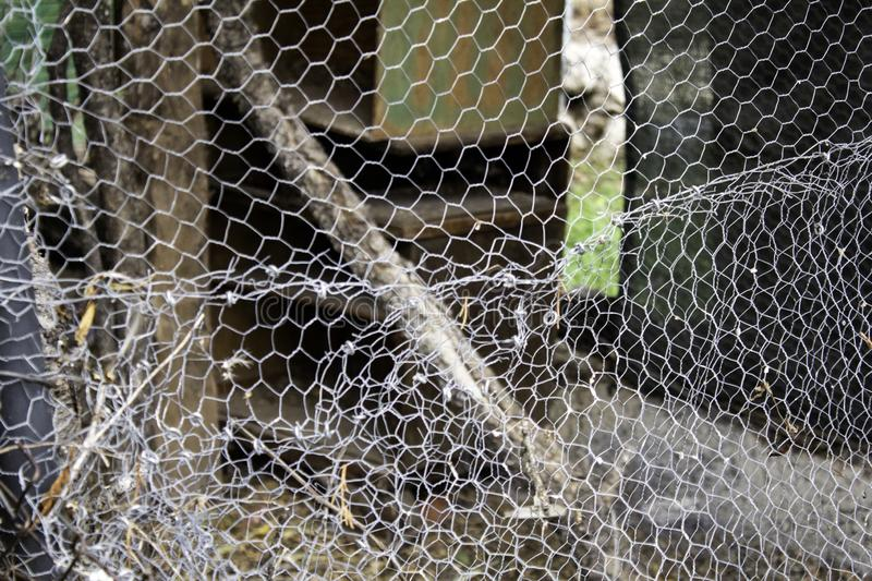 Metal fence mesh. Metal mesh fence, protection and safety, confinement, secure, grate, restriction, captivity, strong, irregular, surface, material, broken stock image