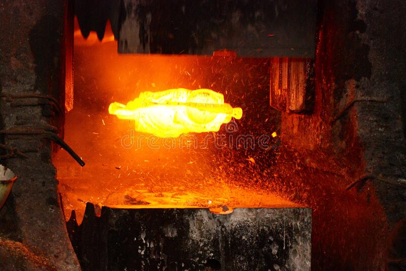 Metal forging. hydraulic hammer shapes the red hot billet. the production of high tech parts.  royalty free stock photo