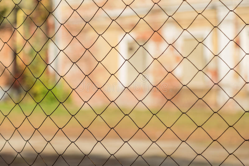 Metal mesh netting on the background of blurred buildings.  royalty free stock photography