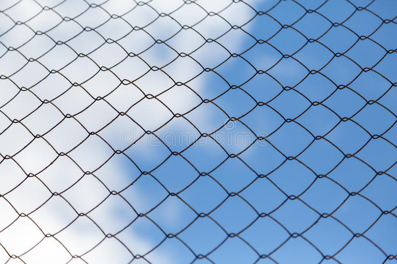 Metal mesh netting on the blue sky background and clouds.  royalty free stock images