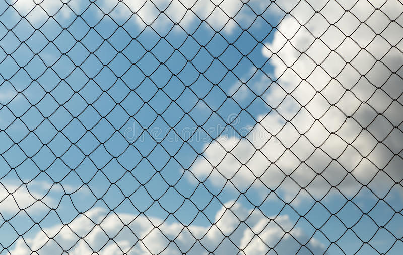 Metal mesh netting on the blue sky background and clouds.  stock photo