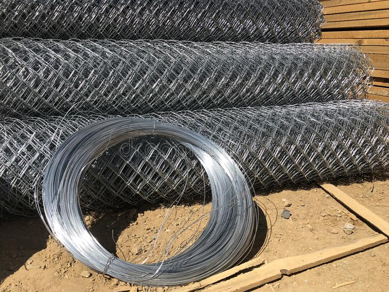 Metal mesh netting rolled into rolls and coils of steel wire. Rolled chain-link fence.  stock image