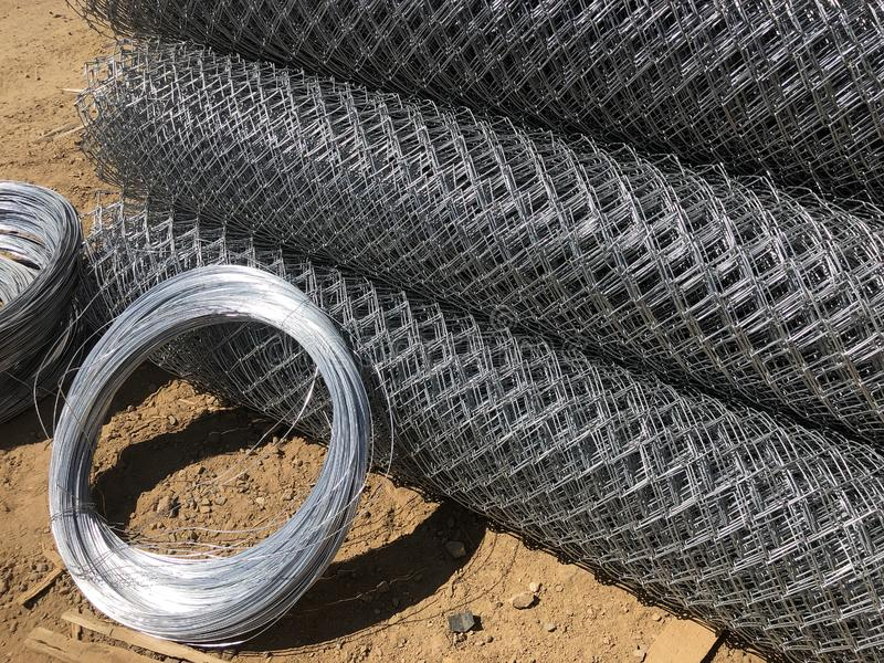 Metal mesh netting rolled into rolls and coils of steel wire. Rolled chain-link fence.  royalty free stock photo