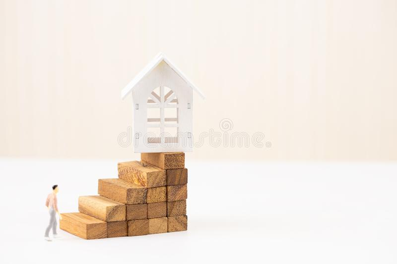 Miniature people small figure walking to model white house on wood block stacking step stair. Property investment. And house mortgage financial concept, Home royalty free stock photo