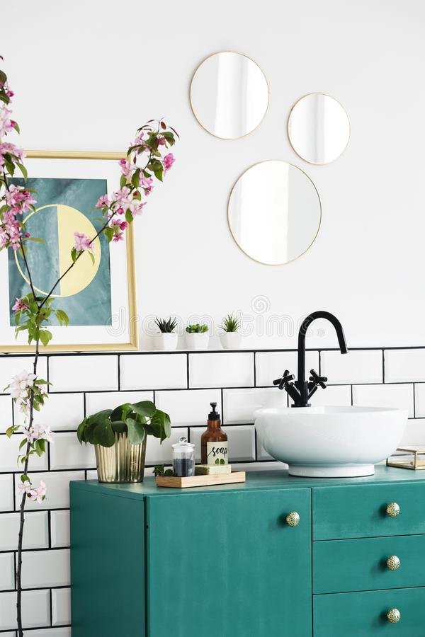Mirrors and poster above green cabinet in modern bathroom interior with plants. Real photo. Concept stock photography