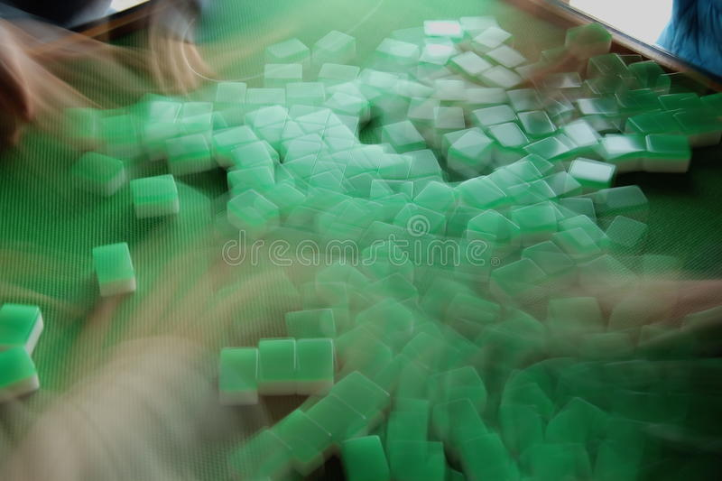 Shuffling Mahjong Tiles. Four players mix green Mahjong tiles in preparation for another turn or round stock photography