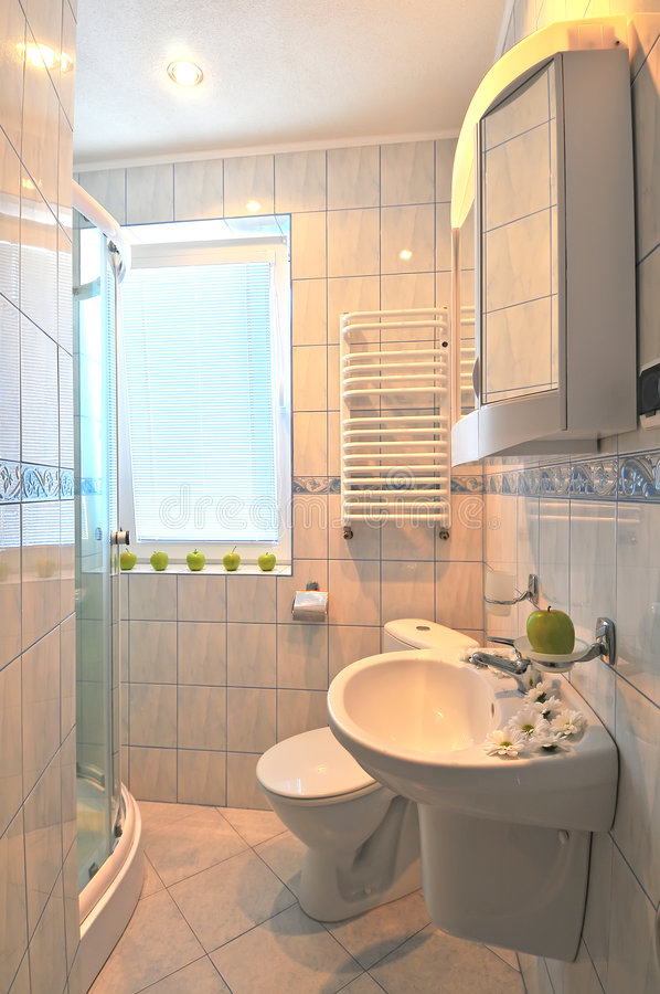 Modern bathroom. A picture of the interiors of a modern bathroom, with shower stall, toilet, sink and mirror. Decorated in a beige colour scheme royalty free stock photo