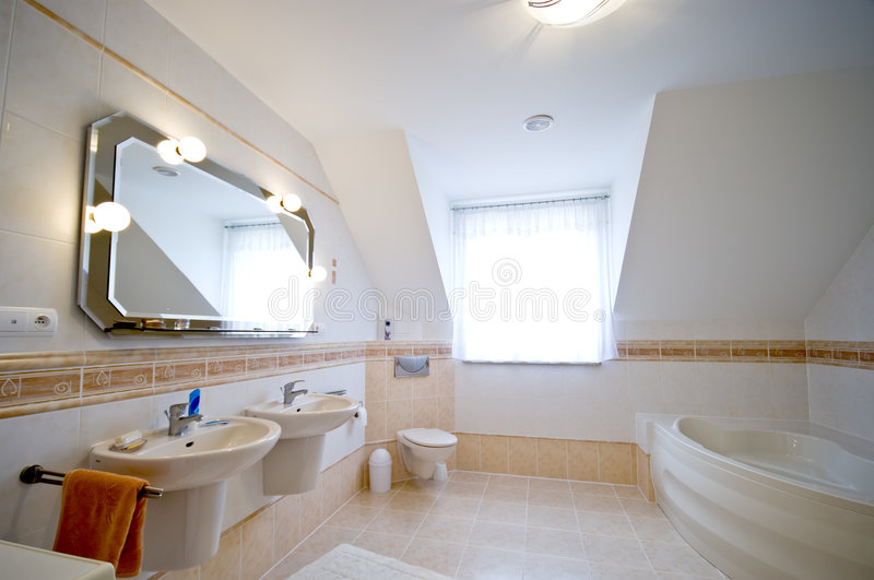 Modern bathroom interior. Interior of a modern loft bathroom with twin basins, bath tub and a large mirror stock photo