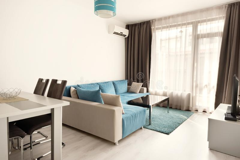 Modern bright and cozy living room interior design with sofa, dining table and kitchen. Grey and turquoise blue studio apartment stock images