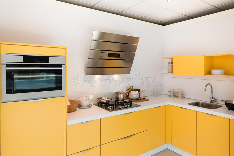 Modern kitchen with steel oven and hood. Modern yellow kitchen with steel oven and hood royalty free stock images